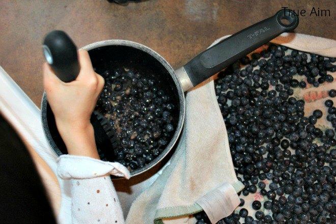 smashing blueberries for jam