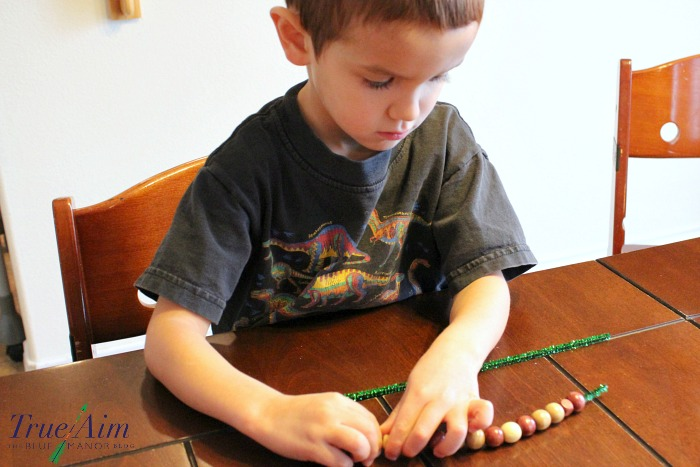 kid-made-acorn-ornaments-stringing-beads